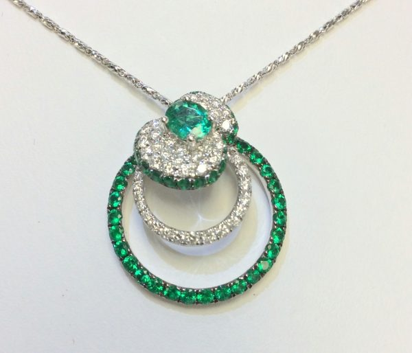 Emeralds and diamonds together in a white gold pendant