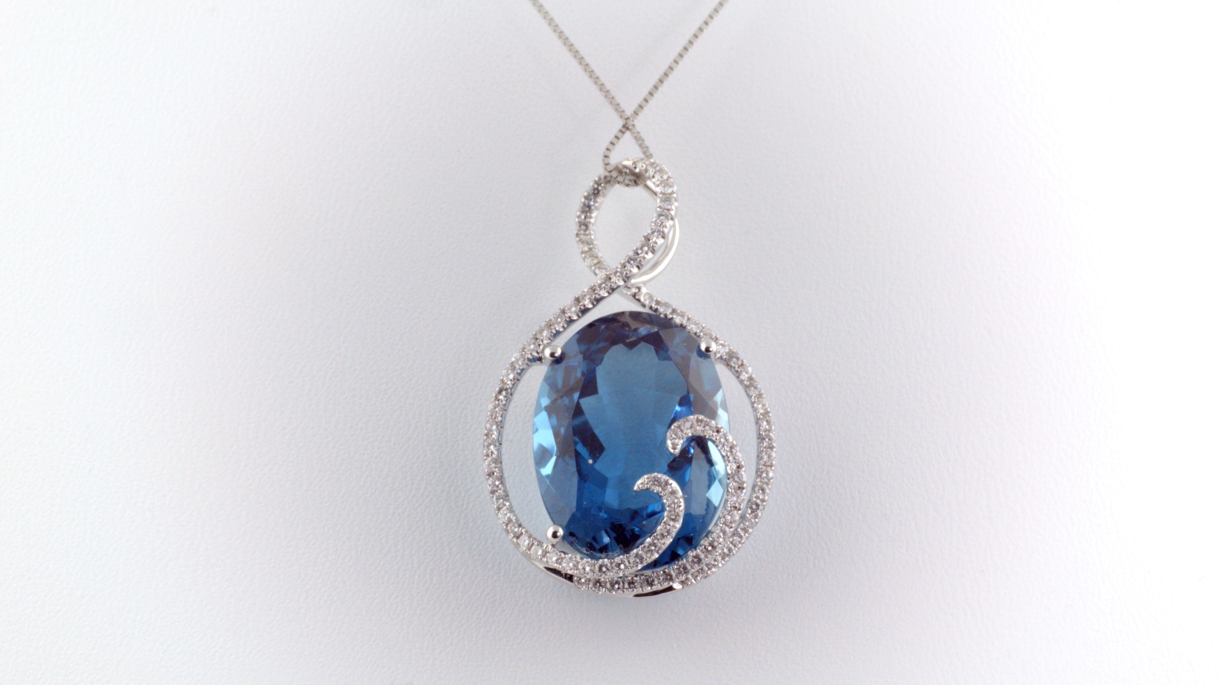 Blue topaz and diamond pendant necklace in 18K white gold.